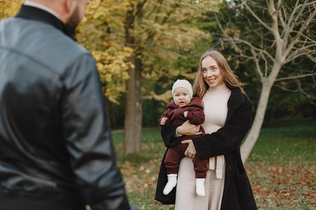 Rodzina w jesiennym parku. mężczyzna w czarnej kurtce. śliczna mała dziewczynka z rodzicami.