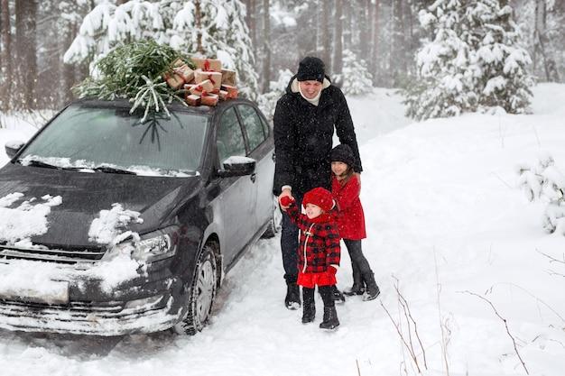 Rodzina w lesie stoi przy samochodzie z choinką i prezentami