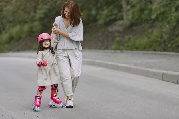 Rodzina w letnim parku. matka w bluzce. mała dziewczynka z rolką.