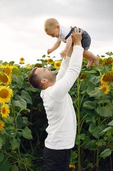 Rodzina w letnim polu ze słonecznikami. ojciec w białej koszuli. słodkie dziecko.