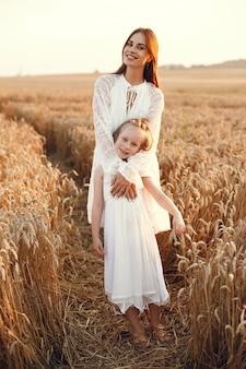 Rodzina w letnim polu. zmysłowe zdjęcie. śliczna mała dziewczynka. kobieta w białej sukni.