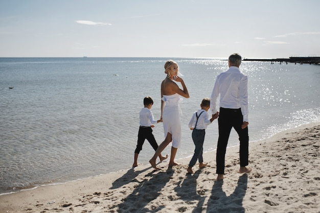 Rodzina w luksusowych ubraniach chodzi boso po piaszczystej plaży w ciepły, słoneczny dzień