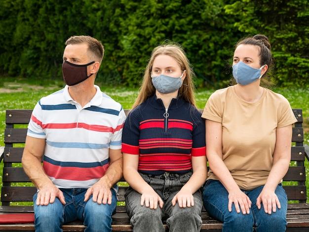 Rodzina w ochronnych maskach na twarz siedzi na ławce w parku