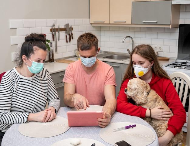 Rodzina w ochronnych maskach oglądająca w domu szokujące wiadomości na tablecie