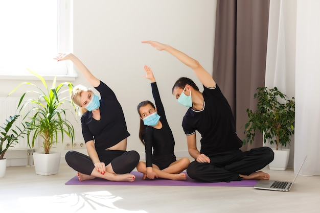 Rodzina w odzieży sportowej, oglądanie wideo online na laptopie i robienie ćwiczeń fitness w domu. szkolenie na odległość z osobistym trenerem, dystans społeczny lub samoizolacja, koncepcja edukacji online
