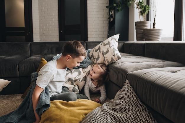Rodzina w piżamie. brat i siostra. noworoczny nastrój. zabawne zdjęcie. baw się poduszkami na podłodze. szare wnętrze.