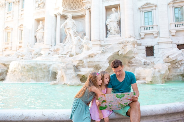 Rodzina w pobliżu fontana di trevi, rzym, włochy. szczęśliwy ojciec i dzieci korzystają z włoskich wakacji w europie.