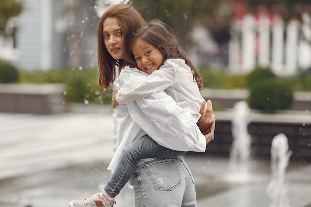 Rodzina w pobliżu miejskiej fontanny. matka z córką bawić się wodą.
