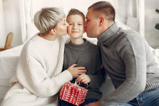 Rodzina w pokoju. mały chłopiec w pobliżu świątecznych dekoracji. matka z ojcem z synem