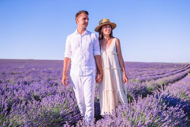 Rodzina w polu kwiatów lawendy o zachodzie słońca w białej sukni i kapeluszu