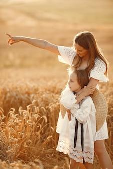 Rodzina w polu pszenicy. kobieta w białej sukni. dziewczyna w słomkowym kapeluszu.