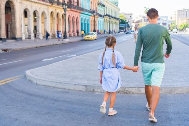 Rodzina w popularnej okolicy w old havana, kuba. małe dziecko i młody tata na zewnątrz na ulicy w hawanie