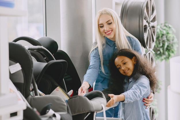 Rodzina w salonie samochodowym. kobieta kupuje fotelik samochodowy. mała afrykańska dziewczyna z mther.