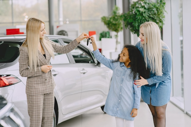 Rodzina w salonie samochodowym. kobieta kupuje samochód. mała afrykańska dziewczyna z mther. manager z klientami.