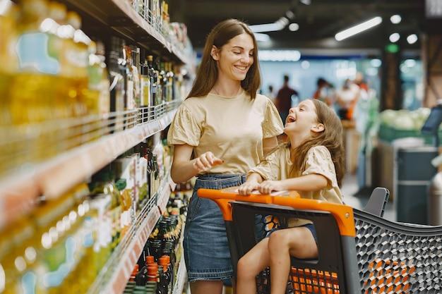 Rodzina w supermarkecie. kobieta w brązowej koszulce. ludzie wybierają produkty. matka z córką.