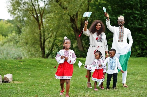 Rodzina w tradycyjne stroje z flagami nigerii w parku