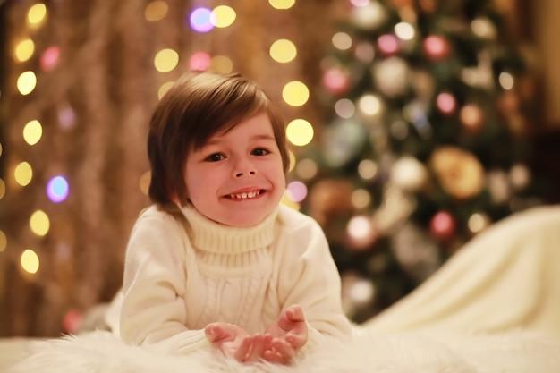 Rodzina w wigilię bożego narodzenia przy kominku. dzieci otwierające prezenty świąteczne. dzieci pod choinką z pudełkami na prezenty. urządzony salon z tradycyjnym kominkiem. przytulny ciepły zimowy wieczór w domu.