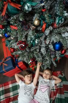 Rodzina w wigilię. dzieci dzieci pod choinką z pudełkami na prezenty. urządzony salon z tradycyjnym kominkiem. przytulny ciepły zimowy wieczór w domu.