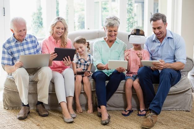 Rodzina wielopokoleniowa korzystająca z cyfrowego tabletu, telefonu komórkowego i wirtualnego zestawu słuchawkowego w salonie