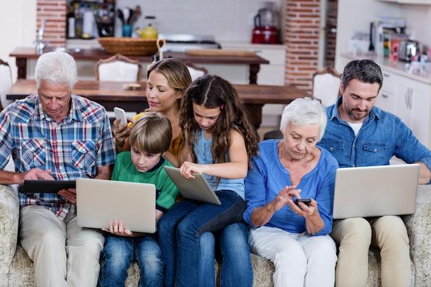 Rodzina wielopokoleniowa korzystająca z laptopa, tabletu i telefonu