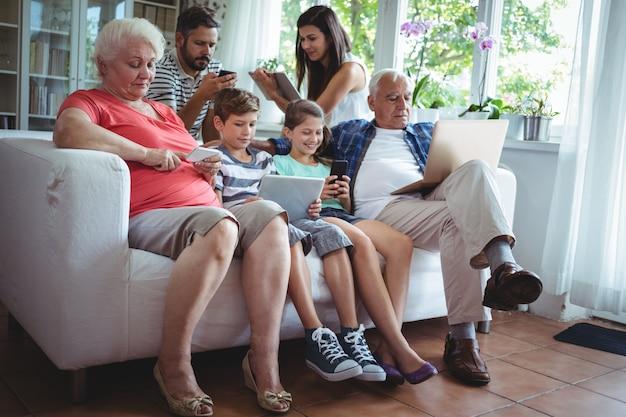 Rodzina wielopokoleniowa korzystająca z laptopa, telefonu komórkowego i cyfrowego tabletu