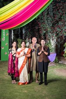 Rodzina witająca gości lub w pozie namaste lub namaskara, patrząc w kamerę w nastroju świętowania