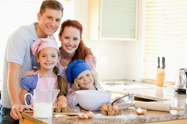 Rodzina wraz ze składnikami do pieczenia za ladą kuchenną