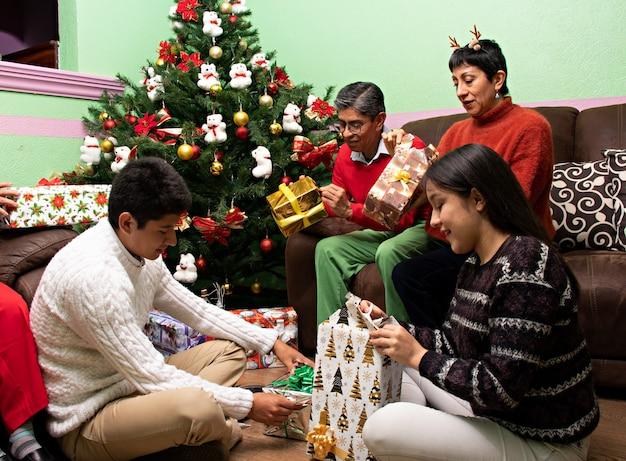 Rodzina wspólnie otwierająca prezenty w boże narodzenie w domu dziadków