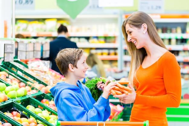Rodzina wybierając owoce i warzywa podczas zakupów spożywczych w supermarkecie