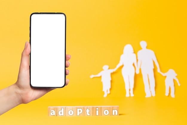 Rodzina wycięta z białego papieru na żółtym tle. drewniane kostki z napisem przyjęcie. po lewej kobieca ręka trzyma smartfon. makieta. pojęcie adopcji.