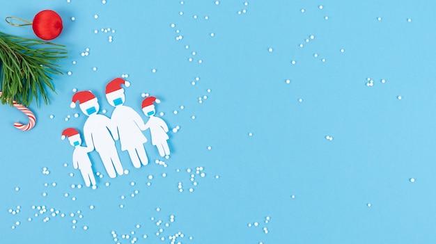 Rodzina wycięta z papieru z maską i świątecznym kapeluszem na niebieskim tle z dekoracją świąteczną. skopiuj miejsce.