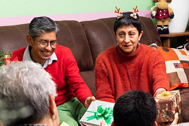 Rodzina wymieniająca się wspólnie prezentami w boże narodzenie w domu dziadków