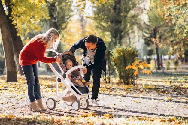 Rodzina z córeczką w wózku spacerowym parku jesienią