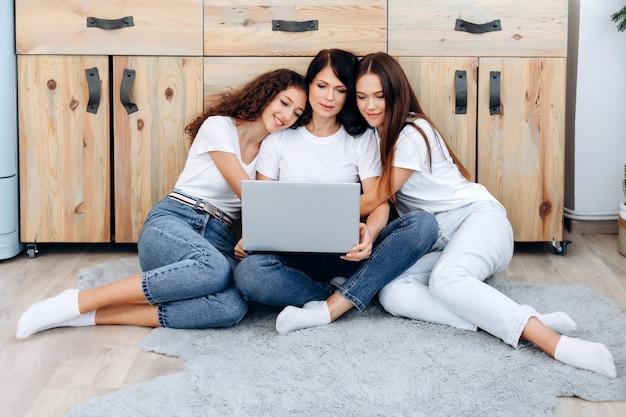Rodzina z dwiema dorosłymi córkami bawiąca się przy użyciu laptopa w domu.