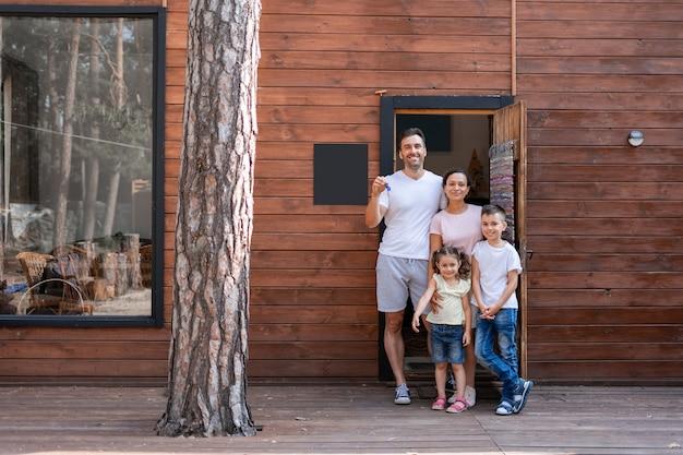 Rodzina z dwójką dzieci stoi na progu ich nowego drewnianego domu za miastem, tata trzyma klucze do nowego domu.
