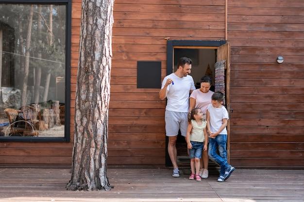Rodzina Z Dwójką Dzieci Stoi Na Progu Swojego Nowego Drewnianego Domu Za Miastem, Tata Trzyma Klucze Do Nowego Domu, Wszyscy Patrzą Na Małą Dziewczynkę Premium Zdjęcia