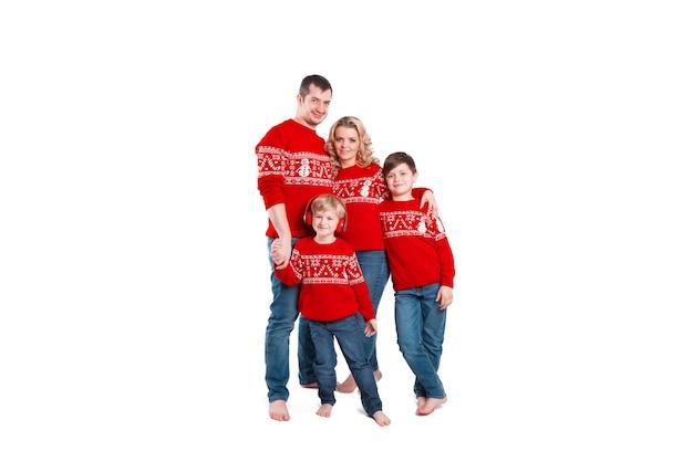 Rodzina z dwójką dzieci w świątecznych ubraniach stojących przytulonych