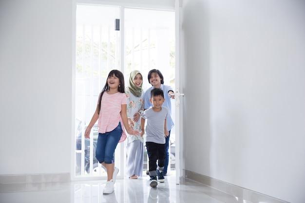 Rodzina z dwójką dzieci wchodzących do nowego domu
