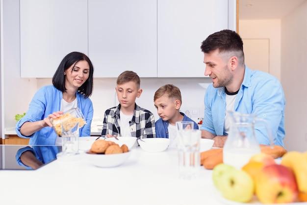 Rodzina z dwoma synami jedzącymi zdrowe poranne śniadanie z płatkami kukurydzianymi i mlekiem