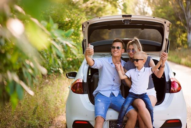 Rodzina z dzieckiem siedzi w bagażniku samochodu przy selfie na telefonie.