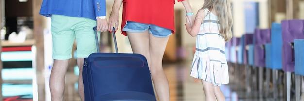 Rodzina z dzieckiem toczy walizkę