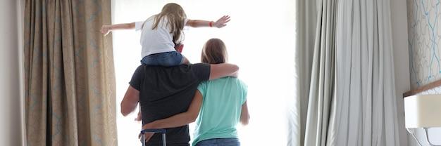 Rodzina z dzieckiem wygląda przez okno w pokoju hotelowym