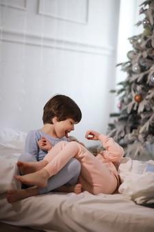 Rodzina z dziećmi bawiąca się na łóżku pod kołdrą podczas świąt bożego narodzenia