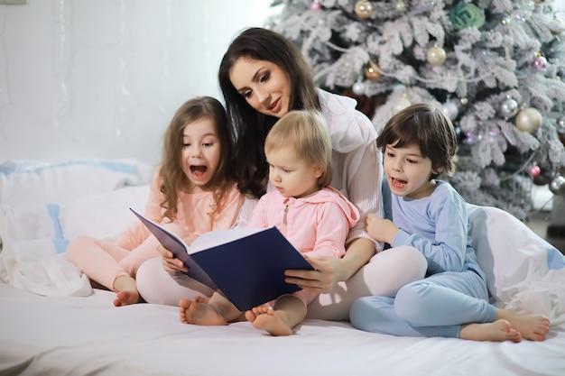 Rodzina z dziećmi bawiącymi się na łóżku pod kołdrą podczas świąt bożego narodzenia.