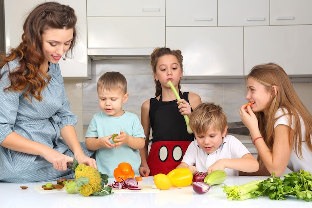 Rodzina z dziećmi kroi warzywa do gotowania
