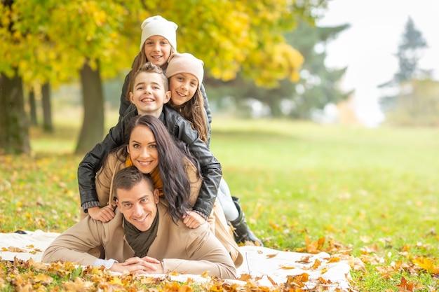 Rodzina z dziećmi leżąca na kocu tworząca ludzką piramidę w naturze w jesienny dzień.