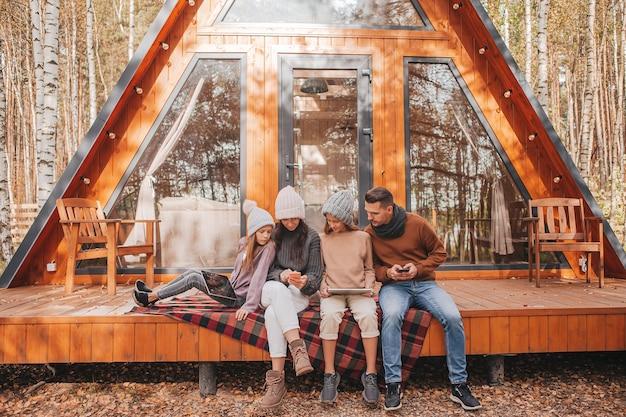 Rodzina z dziećmi na tarasie swojego domu w jesienny dzień, każdy z własnym gadżetem