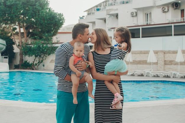 Rodzina z dziećmi pozowanie w basenie. wakacje w hotelu