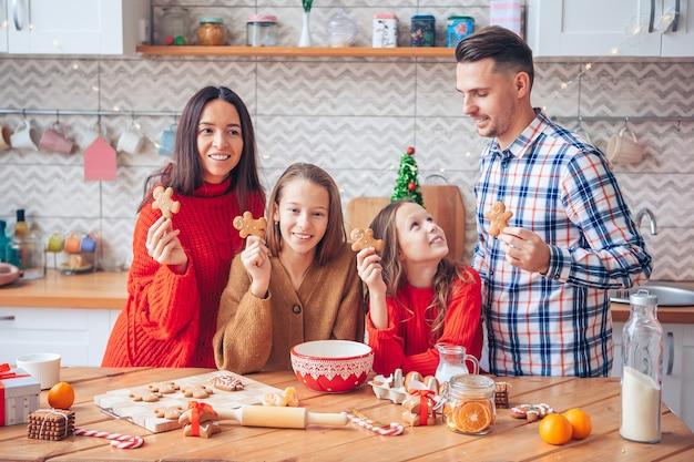 Rodzina z dziećmi przygotowuje ciasteczka na boże narodzenie w kuchni. wesołych świąt i wesołych świąt.