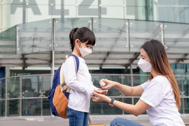 Rodzina z dziećmi w masce na twarz w centrum handlowym. matka i córka noszą maskę na twarz podczas epidemii koronawirusa i grypy. ochrona przed wirusami i chorobami, dezynfekcja rąk w zatłoczonym miejscu publicznym.